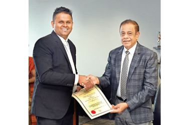 Hemasiri Fernando, Chairman of the Board and Roshan Buthgama, Director and Managing Director of Skylift Container Depot and Logistics (Private) Limited exchanging agreement