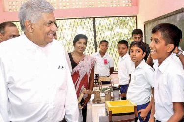 Prime Minister Ranil Wickremesinghe speaks to a student at the educational exhibition at Karandeniya Madya Maha Vidyalaya, which he opened on Wednesday. Picture by Sulochana Gamage