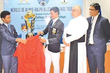 Gateway College captain RashaneWijewardene (second from left) and S.. Thomas' College captain DS Ebenezer (thirdfrom left) unveil the Neville de Alwis-Ralph Alles Trophy . Also in the picture from left Dr. Harsha Alles-Chairman of Gateway, Rev. Marc Billimoria - the Warden of S. Thomas' College, Anura De Silva - President of Football Federation of Sri Lanka and Anura Shantha - Prefect of Games of S. Thomas' College. PIcture by Herbert Perera
