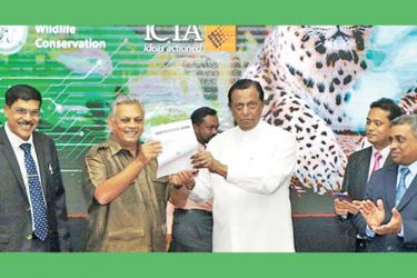 Tourism and Wildlife Minister John Amarathunga issues the first E-permit at the launch ceremony yesterday.  Picture by Chaminda Niroshana