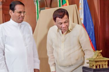 President Maithripala Sirisena admires the memento together with President Rodrigo Duterte in the Philippines  yesterday.  Picture by Sudath Silva.