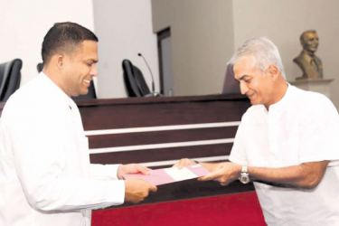 Former Sri Lanka cricketer Sidath Wettimuny receiving his National Sports Council letter of appointment from Sports Minister Harin Fernando at the Duncan White Auditorium yesterday.