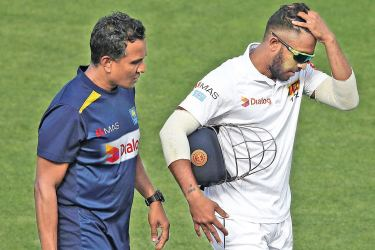 Kusal Mendis leaves the field with the helmet tucked under his injured right hand on the first day of their tour-match against CA XI at Hobart on Thursday.