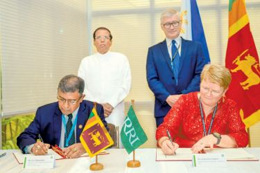 IRRI's Research Deputy Director General Jacqueline Hughes and the  Foreign Affairs Ministry's  Bilateral Affairs Additional Secretary  Sumith Nakandala sign the agreement watched by President Maithripala  Sirisena and IRRI's Director General Matthew Morell yesterday. Pictures by Sudath Silva