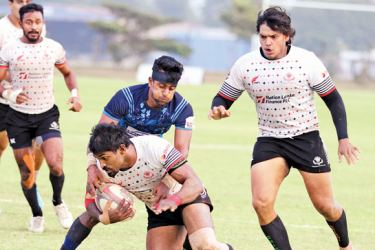 A CH and FC player his well held by an Air Force player but has more support coming his way from skipper Rohitha Rajapaksa in their Dialog 'A' Division league rugby match played at Air Force grounds Ratmalana yesterday which CH and FC won 29-22. Picture by Samantha Weerasiri