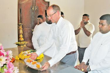 Canadian High Commissioner David Mackinnon offers a tray of flowers at Ruhunu Maha Kataragama Devalaya yesterday. Picture by Kataragama Roving Corr.