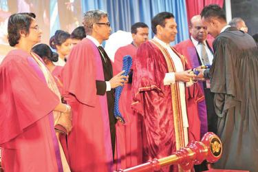 Health Minister Dr. Rajitha Senaratne hands over an appointment letter to a newly recruited male nurse while other officials look on.