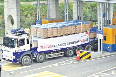 South Korean trucks carrying 500 tonnes of flour for North Korea drive through the South's inter-Korean transit gate in Paju, north of Seoul.