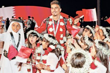 Qatar's forward Akram Afif (up) poses for a photograph at Doha airport, in Doha on Saturday as the Qatari national football team's players and staff come back from the United Arab Emirates with the trophy after winning the 2019 AFC Asian Cup football tournament.- AFP