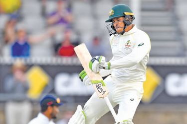 Australia's Usman Khawaja (R) celebrates reaching his century during day three of the second Test cricket match against Sri Lanka at the Manuka Oval Cricket Ground in Canberra on Sunday. - AFP