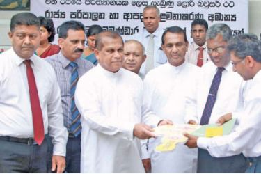Minister Ranjith Madduma Bandara presents the key to a water bowser to a district secretary. Picture by Shan Rambukwella