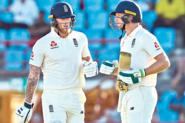 Ben Stokes (L) and Jos Buttler (R) of England during their partnership on day one of the 3rd and final Test against West Indies at Darren Sammy Cricket Ground, Gros Islet, Saint Lucia, on Saturday, - AFP