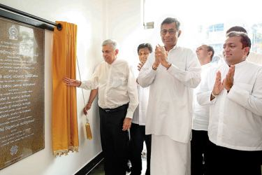 Prime Minister Ranil Wickremesinghe opens the newly built Bandaragama Public Market Complex on Monday, as Minister Patali Champika Ranawaka looks on.