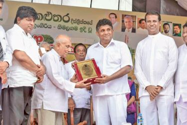 Minister Sajith Premadasa presents a memento to former Minister Indradasa Hettiarachchi after whom the model village is named.