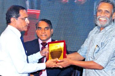 Elections Commission Chairman Mahinda Deshapriya presents a token of appreciation to Associated Newspapers of Ceylon Limited (ANCL) Deputy General Manager (Production, Planning and Marketing) Rasantha Chandrathileke to recognise ANCL's contribution to the print media, at the 30th anniversary celebration of PAFFREL in Colombo yesterday.