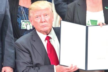 US President Donald Trump signs an executive order to start the Mexico border wall project at the Department of Homeland Security facility in Washington, DC, on January 25, 2017. - AFP