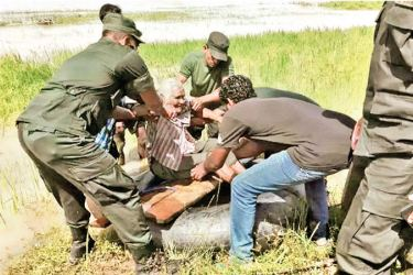 Army personnel assist a flood victim in Mullaitivu in this December 2018 file photo.  Picture by Vavuniya Gr. corr.