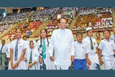 President Maithripala Sirisena flanked by schoolchildren arriving at the Sugathadasa Stadium to inaugurate the Daruwan Surakimu national programme yesterday. Picture by President's Media Division.