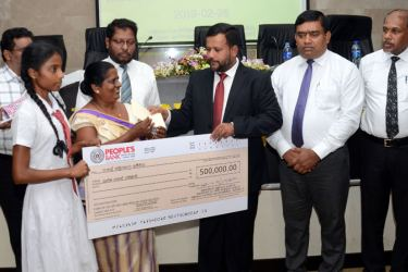Minister of Industry & Commerce, Rishad Bathiudeen presenting' funds' to a school to initiate a Cooperative Society  Picture By: Wimal Karunathilake