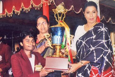 The victorious Chitra House Captain of Sri Sumangala Girls College (National School) Panadura receives the Overall Athletic Championship Cup, from the chief guest Mrs. Apsari Tillakaratne (Women's Cricket Chief, Sri Lanka) with the participation of Principal Mrs Nepala (centre). - (Picture by Kalutara Central Special Corr. H L Sunil Shantha)