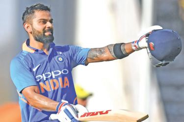 Indian captain Virat Kohli celebrates after scoring a century during the second one-day international (ODI) against Australia at the Vidarbha Cricket Association Stadium in Nagpur on Tuesday - AFP