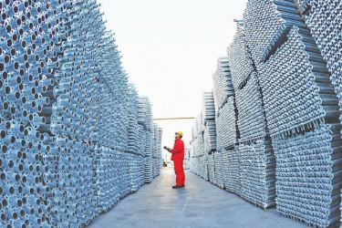A staff worker checks out the products that have rolled off the assembly line at an equipment manufacturer, which produces new types of building materials, in Leting, Hebei province. [Photo/Xinhua]