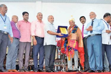 Minister Rauff Hakeen handing over the award to P.M. Kalanderlebbe, while others look on. Picture by I.L.M. Rizan, Addalaichenai Central Corr.