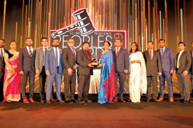 Nadeeja Karunathilaka, General Manager, International Market Development at Ceylon Biscuits Limited (CBL), receives the award from Sathika Wickramasinghe, Project Chairperson for SLIM-Nielsen People's Awards 2019. Also in the picture are members of the Marketing and Sales teams of CBL