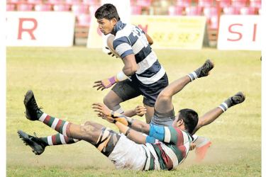 A St. Joseph's College player storms ahead after evading a tackle from a Zahira College player in their Singer League Division one rugby match played at Havelock Park yesterday which St. Joseph's won 47-5 (picture by Tilak Perera)