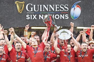 Wales' lock Alun Wyn Jones (C) holds up the trophy after being crowned Six Nations rugby champions after beating Ireland at the Principality Stadium in Cardiff, on Saturday, - AFP