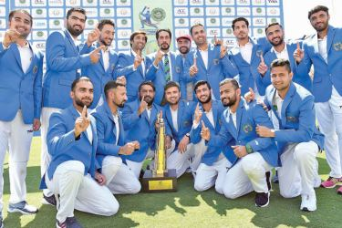Afghanistan's team members pose with the trophy after winning the Test cricket match between Afghanistan and Ireland at the Rajiv Gandhi International Cricket Stadium in the northern Indian city of Dehradun on March 18. AFP