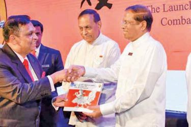 CIABOC Director General Sarath Jayamanne presents a copy of  the National Action Plan to President Maithripala Sirisena, at the  launch on Monday, as Speaker Karu Jayasuriya, Western Province Governor  Azath Salley and North Central Province Governor Sarath Ekanayake look  on.  Picture courtesy President's Media Division