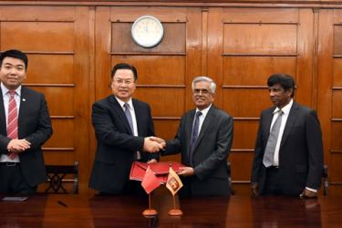 Finance Ministry Secretary Dr. R. H. S. Samarathunga and Chinese Ambassador Cheng Xueyuan shake hands after signing the agreement while others look on.