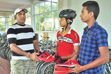 Sugath Edirisinghe donating sports gear to cyclist G.K. Danidu Dilshan and volleyball player W.D. Kasun Dilshan.
