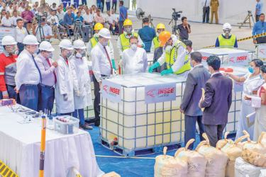 President Maithripala Sirisena walks past hauls of cocaine which were to be destroyed yesterday at a warehouse facility in Gonawela in Kelaniya. INSEE Ecocycle which undertook the mammoth task last year assisted with the processing of the drugs this year. The 769 Kilogrammes of cocaine which was diluted yesterday was sent to the Kiln Cement plant in Puttalam. Picture by Wasitha Patabendige