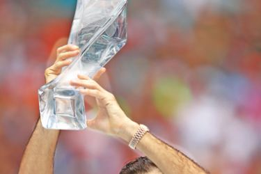 Roger Federer of Switzerland celebrates with the winner's trophy against John Isner of USA in the final of the Miami Open tennis tournament on Sunday. - AFP