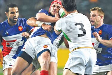 France's Gabin Villiere (centre L) fights for the ball during their match against Portugal on the first day of the Rugby Sevens Tournament in Hong Kong on Friday. - AFP