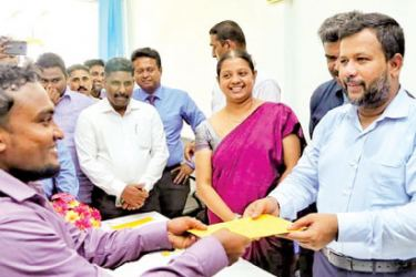 Minister of Industry Commerce, Resettlement of Protracted Displaced Persons & Cooperative Development Skills Development and Vocational Training, Rishad Bathiudeen hands over a bonus payment to a worker at Pulmoddai mines of Lanka Mineral Sands Ltd on April 8