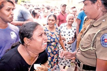A sobbing woman asks a police officer for information, outside the National Hospital, Colombo, on Sunday. Picture by Roshan Pitipana