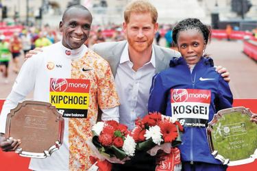 Kenya's Eliud Kipchoge and Brigid Kosgei celebrate winning the respective men's and women's elite races with the trophies as they pose with Britain's Prince Harry.