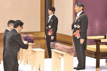 Japan's new Emperor Naruhito receives the Imperial regalia of sword and jewel as proof of succession at the ceremony at Imperial Palace in Tokyo yesterday. Standing at left is Crown Prince Akishino.