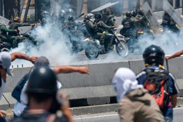 Anti-government protesters clash with security forces near La Carlota military base in Caracas.