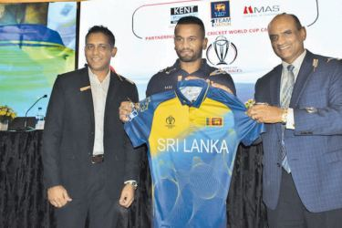 Shirendra Lawrence, Chief Operating Officer, MAS Holdings the clothing sponsor of the Sri Lankan cricket team handing over a replica of a T-Shirt to Sri Lanka captain Dimuth Karunaratne. Rashmika Peiris, Director Business MAS Active is also present.
