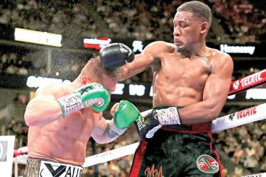 Daniel Jacobs (R) punches Canelo Alvarez during their middleweight unification fight at T-Mobile Arena on May 04 in Las Vegas, Nevada. AFP