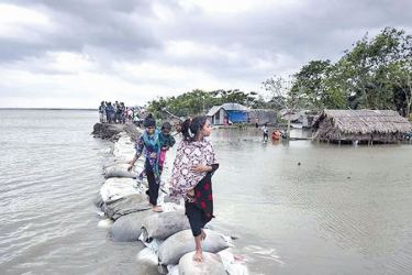 Bangladeshi children walk over the top of a sandbag embankment that was breached by high waters.