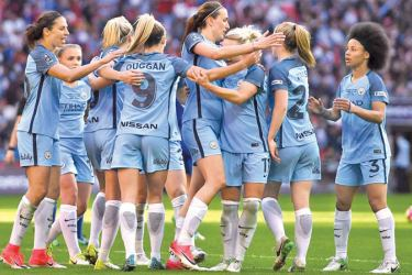 Manchester City players celebrate winning the Women's FA Cup with the trophy.