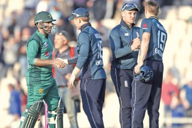 England's captain Eoin Morgan (2nd L) and Pakistan's captain Sarfaraz Ahmed (L) shake hands after the second One Day International (ODI) at The Ageas Bowl in Southampton on Saturday. England beat Pakistan by 12 runs and take 1-0 lead in the five-match series.  - AFP