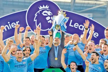 Manchester City manager Pep Guardiola lifts the trophy as they celebrate winning the Premier League.