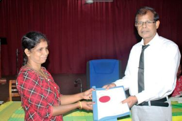 A resettled woman receives a deed.