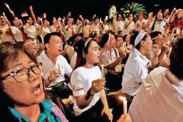 People hold a vigil for the victims of the suicide bomb attacks in Surabaya.